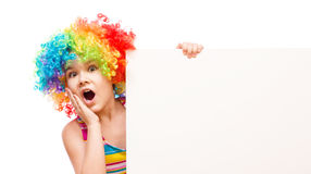 Girl in clown is holding blank banner Royalty Free Stock Photos