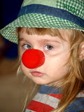 Sad girl with red clown nose. Portrait of sad young girl in red clown nose Royalty Free Stock Photo
