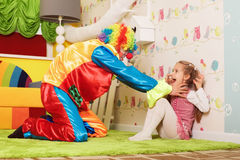 Girl and a clown playing on the green carpet. Stock Photography