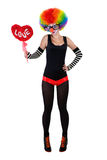 Girl in a clown suit holding a red heart Stock Photography