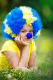 Girl in clown wig with blue nose is lying on the green grass Stock Images