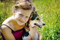 Girl clung to her dog and feels happy. Good day of summer_ stock images