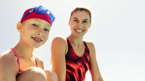 Smiling girl with swimming trainer. Girl and coach on swimming pool edge. Smiling child with swimming trainer against bright sky stock images
