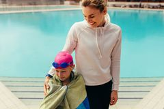Girl with coach at swimming pool. Girl wrapped in towel standing with a women by the pool. Girl child with coach at swimming pool stock image