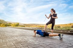 Girl coach training hard a man through push ups. Beautiful athlete girl coach training very hard a men while timing the push ups with chronometer stock image