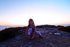 Girl on coastline at sunset Stock Image