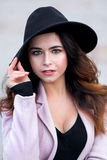 The girl in a coat with black hat on head. The girl`s portrait in a coat and a black hat on the head also looks in a shot, eyes of different color Royalty Free Stock Photo