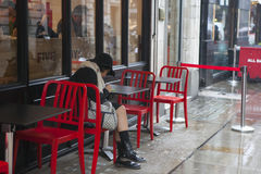 Girl in coat and hat sitting on a red table in an outdoor cafe in the rain Royalty Free Stock Images