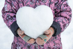 Girl in coat and mittens holding a snowball in the shape of a heart. Stock Photos