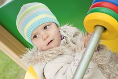 The girl in a coat on a playground Royalty Free Stock Images