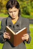 Girl in coat reads book Royalty Free Stock Photography