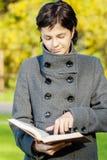 Girl in coat reads book Stock Image