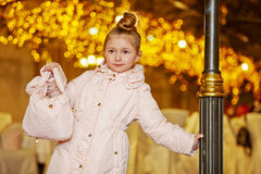 Girl in coat stands, leaning one hand on lamp post Stock Photo