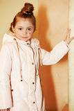 Girl in coat stands, leaning one hand on pillar Royalty Free Stock Photos