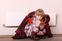 Girl in coat warm  near radiator. Crisis. Royalty Free Stock Photo
