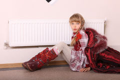 Girl in coat warm  near radiator. Crisis. Stock Image