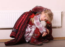 Girl in coat warming herself near a radiator Stock Photos