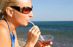 The girl with a cocktail. The girl is drinking a cocktail on the background of the sea Stock Photo