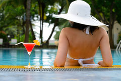 Girl with a cocktail at the edge of the swimming pool Stock Images