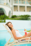 Girl with cocktail enjoying laying onchaise-longue Stock Photo