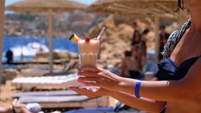 Girl with a Cocktail in Hands on the Beach of Egypt, the Red Sea. Slow Motion.  stock footage