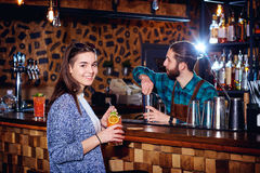 A girl with  cocktail smiles behind counter at the bar Royalty Free Stock Images