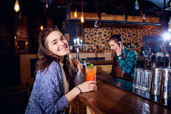 A girl with  cocktail smiles behind counter at the bar Royalty Free Stock Image