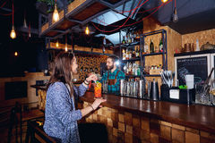 A girl with  cocktail smiles behind counter at the bar Stock Images