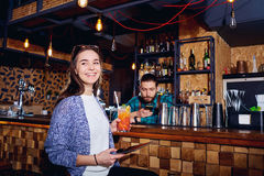 A girl with  cocktail smiles with tablet behind counter at the b Stock Images