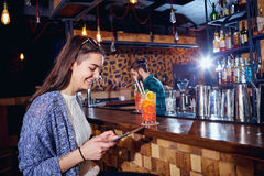 A girl with  cocktail smiles with tablet behind counter at the b Stock Photos