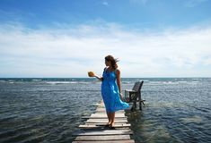 The Girl with a Coconut. The girl posing with a coconut at the end of a wooden pier on Roatan island (Honduras Stock Photography