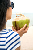 Girl with coconut on a beach Royalty Free Stock Image