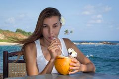 Girl with coconut cocktail. Young girl with coconut on the see side stock photo