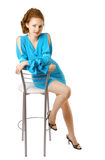 Girl in a coctail dress on the high chair Stock Images