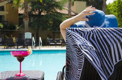 Girl with coctail drink by the pool Stock Image