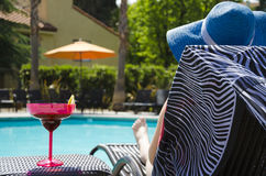 Girl with coctail drink by the pool. Girl in blue hat with coctail drink by the pool Royalty Free Stock Photography