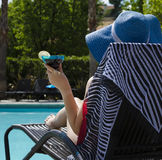 Girl with coctail drink by the pool. Girl in blue hat with coctail drink by the pool Royalty Free Stock Images