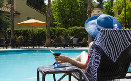 Girl with coctail drink by the pool. Girl in blue hat with coctail drink by the pool Stock Photography