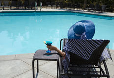 Girl with coctail drink by the pool. Girl in blue hat with coctail drink by the pool Stock Images
