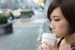 Girl with coffee. Asian girl holding cup of coffee at street in raining day in Taipei, Taiwan Royalty Free Stock Photos