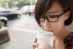 Girl with coffee. Asian girl holding cup of coffee at street in raining day in Taipei, Taiwan Royalty Free Stock Images