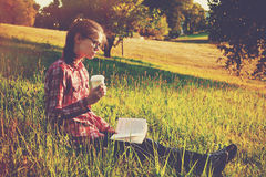 Girl with coffee cup and book Stock Photography