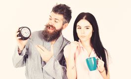 Girl with coffee cup, man holds clock in hand. Couple, family woke up on time. Couple in love, young family in pajama royalty free stock photography