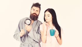 Girl with coffee cup, man holds clock in hand. Perfect morning concept. Couple, family woke up on time. Couple in love royalty free stock image
