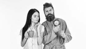 Girl with coffee cup, man holds clock in hand. Perfect morning concept. Couple, family woke up on time. Couple in love. Girl with coffee cup, men holds clock in stock photo