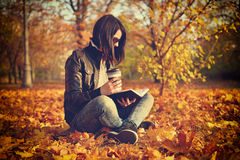 Girl with coffee cup reading a book Stock Photo
