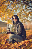 Girl with coffee cup sitting on leaves in park Royalty Free Stock Photos