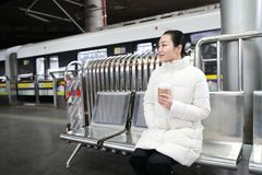 The girl With coffee in his hand is sitting in a chair and waiting metro. The girl is sitting in a chair and waiting metro at shanghai railway station Royalty Free Stock Photo