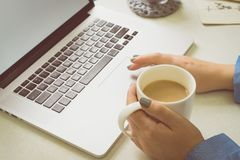 Girl coffee laptop. Girl enjoys a laptop and drinks coffee royalty free stock photos