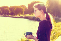 Girl with coffee near river Stock Image